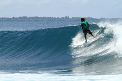 Surfer riding fast on tropical blue wave Stock Images