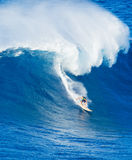 Surfer riding giant wave. Extreme surfer riding giant ocean wave in Hawaii Royalty Free Stock Photo