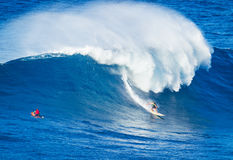 Surfer riding giant wave. Extreme surfer riding giant ocean wave in Hawaii Royalty Free Stock Photos