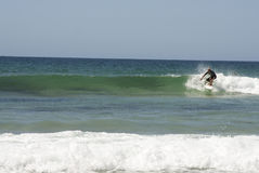 Surfer riding wave Stock Images