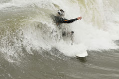 Surfer riding wave. A male surfer is covered in water as he rides a powerful wave Royalty Free Stock Images
