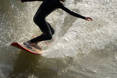 Surfer riding wave. A male surfer is covered in water as he rides a powerful wave Stock Photography