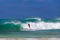 Surfer riding a wave on Hikkaduwa beach Stock Photo