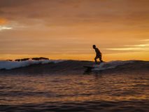 Surfer riding wave at Magnific Rock, Nicaragua at sunset Stock Photos