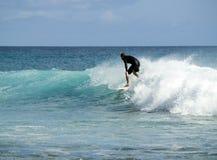 Surfer riding waves at sea Stock Photo