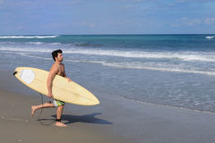 Surfer Running on Beach Stock Photography