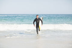 Surfer running on the beach with a surfboard. Surfer with a surfboard running on the beach on a sunny day Stock Images