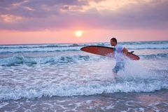 Surfer running on coast in Indonesia. Bali, Kuta Royalty Free Stock Photo