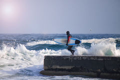 Surfer runs into water wearing a wetsuit. Wave splash. waterproof suit Royalty Free Stock Photo