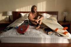 Surfer`s morning. Surfer wake-up with his boards in bed Royalty Free Stock Images