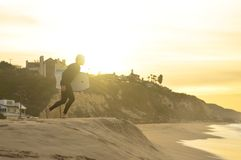 Surfer on sandy beach at sunrise Royalty Free Stock Photos