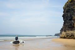 Surfer se tenant avec le conseil sur la plage de ballybunion Photos libres de droits