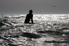 Surfer at sea. A young male surfer waiting for a wave stock image