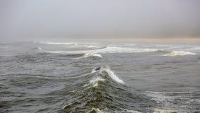 Surfer seul attrapant une vague un jour sombre froid photos stock
