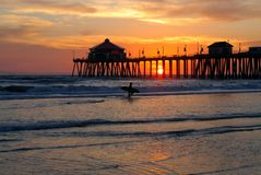 Surfer Silhouette. In Foreground of Pier At Sunset Stock Photo