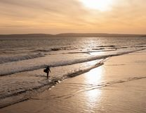 Silhouetted surfer walking out of the sea carrying a surfboard. A surfer in silhouette carrying a surfboard walking out of the sea with the glow of the sun on Royalty Free Stock Photography