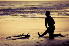 Surfer silhouette during sunset. Silhouette of a surfer sitting near the ocean during sunset Royalty Free Stock Photos