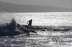 Surfer silhoutted contre les ondes argentées Photographie stock