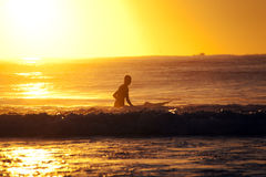 Surfer sits on the surfboard at sunrise Stock Images
