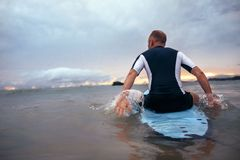 Surfer sits on surfboard on the waves in sunset time Stock Image