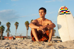 Surfer sitting on the beach with surfboard Stock Photography