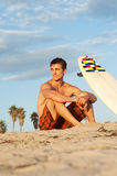 Surfer sitting on the beach with surfboard Stock Photo