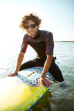 Surfer sitting on his surf board in water wearing swimsuit Royalty Free Stock Photos