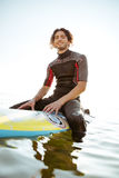 Surfer sitting on his surf board in water wearing swimsuit. Smiling young male surfer sitting on his surf board in water wearing swimsuit and looking at camera Stock Photo