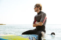 Surfer sitting on surf board with hands crossed in ocean Stock Photography