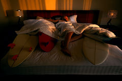 Surfer sleeping. Wth his boards in bed Stock Images