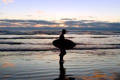 Surfer am Sonnenuntergang auf dem Strand Stockfoto