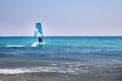 Surfer Spending Time on Outdoor Water Sport Adventure. Clear Sky and Blue Wave. Person Balancing on a Windsurfing Board. With Sail. Vacation Activity ideas royalty free stock photo