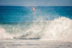 Surfer springt an Bord auf Welle Stockfoto