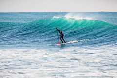 Surfer on stand up paddle board on blue wave. Winter surfing in ocean. Surfer on stand up paddle board on wave. Winter surfing in sea Stock Images