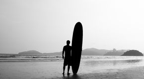 The Surfer. Surfer standing on the beach, close to the sea, contemplating the waves stock photos
