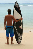 Surfer standing on beach with funky arty surfboard Stock Photography