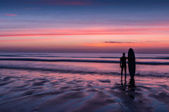 Surfer standing on beach holding surfboard at sunset. Silhouette of a surfer on coast in the evening light Stock Photography