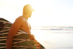 Surfer standing on beach looking at waves during sunset Stock Images