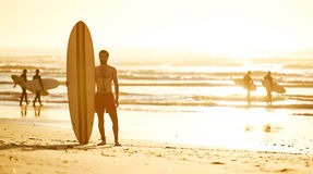 Surfer standing on beach with other surfers behind him Stock Images