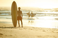 Surfer standing on beach with other surfers behind him. Caucasian male surfer holding a retro surfboard under his arm while looking sideways off camera, with Royalty Free Stock Photos