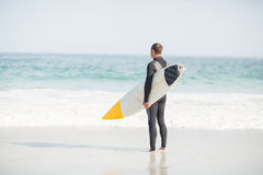 Surfer standing on the beach with a surfboard. Surfer with a surfboard standing on the beach on a sunny day Royalty Free Stock Photography