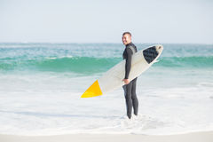 Surfer standing on the beach with a surfboard. Surfer with a surfboard standing on the beach on a sunny day Stock Photography