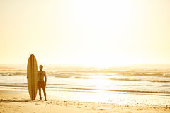 Surfer standing with his surfboard upright beside him on beach. Landscape image of male surfer posing with his surfboard standing upright beside him on the beach Royalty Free Stock Images