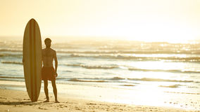 Surfer standing with his surfboard upright beside him on beach. Landscape image of male surfer posing with his surfboard standing upright beside him on the beach Royalty Free Stock Photo