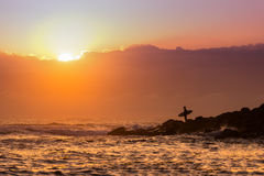 Silhouette of a surfer at sunrise or sunset. Standing at the edge of a point break Royalty Free Stock Images