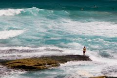Surfer standing on a rock Stock Photo