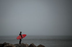 Surfer standing on the rock jetti Royalty Free Stock Photos