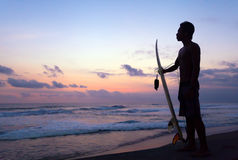 Surfer standing at sunset in Ocean Stock Image