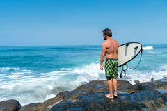 A surfer stands on the rocks royalty free stock images