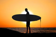 Surfer at sundown. A young male surfer with a surfboard under his arm, with sundown in the background royalty free stock photo